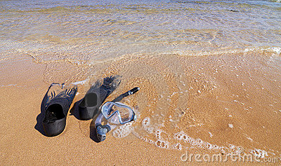 Snorkeling set lying on sand partly in sea water