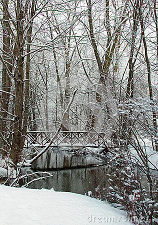 Snow covered bridge over creek