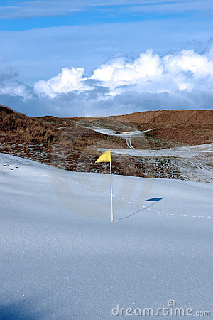 Snow covered links golf course with yellow flag