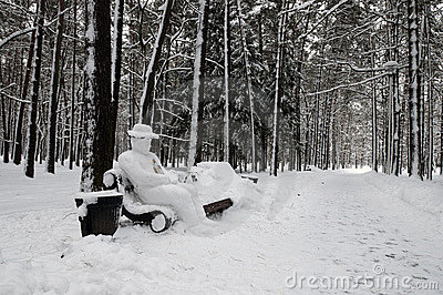Snow-covered park bench with yeti man