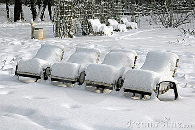 Snow-covered park-chairs in a municipal park