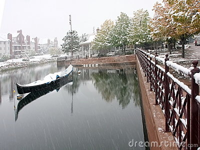 Snow falling into pond with boat