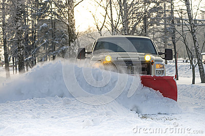 Snow plow doing snow removal after a blizzard Stock Photo