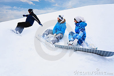 Snow splashes from board near two girls