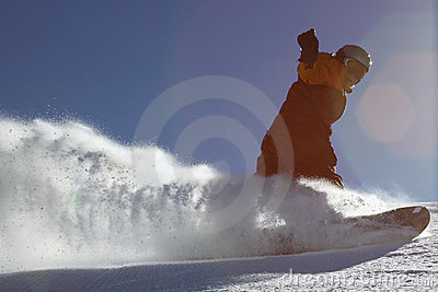 Snow splashes under snowboarder