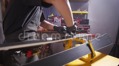 Ski or snowboard tuning and reapair concept  Winter shop worker doing base  repair and service  Mounting, male