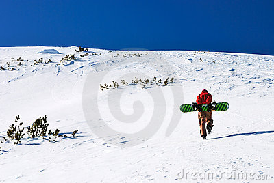 Snowboarder climbing snow slope
