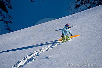 Snowboarder climbing to the peak
