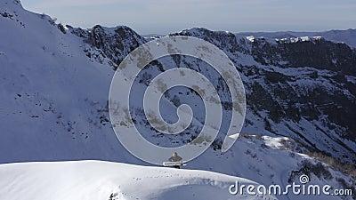 Snowboarder con tablero de nieve escalando en pico nevado en invierno vista de drones de montaña almacen de metraje de vídeo