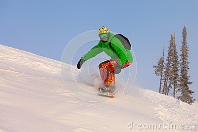 Snowboarder doing a toe side carve with deep blue sky in backgro