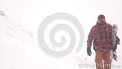 Snowboarder geht durch einen Blizzard Vorstand stock video footage