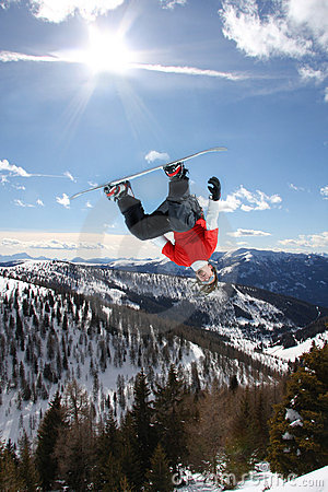 Snowboarder jumping against sky
