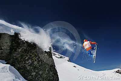 Snowboarder jumping from a cliff