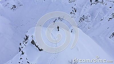 Snowboarder montando en snowboard desde el pico de nieve en la vista salvaje de los drones de montaña almacen de video