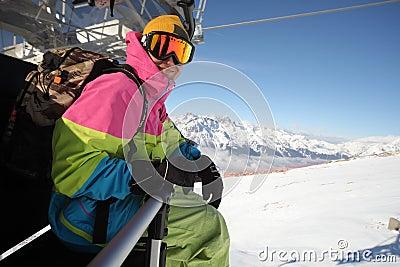 Snowboarder riding chair lift at ski resort