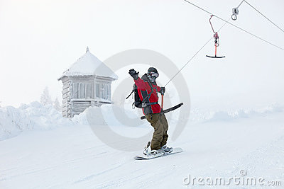 Snowboarder rises up the mountain on sky-lift