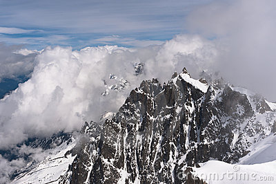 Snowbound mountain peaks in clouds