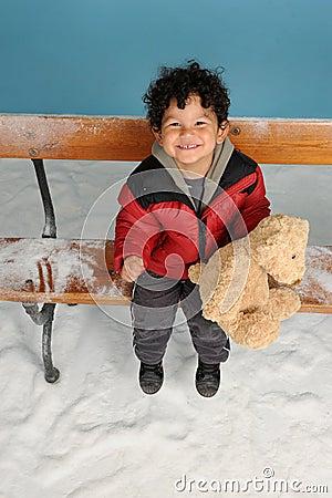 Snowing on a little boy with teddy bear