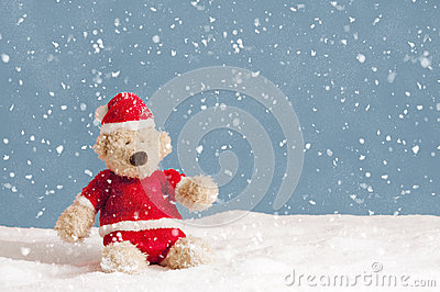 Snowing on teddy bear in christmas clothes