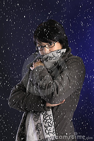 Snowing on young woman with wintercoat and shawl