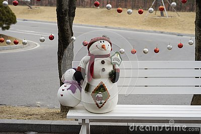 A snowman holding a welcome sign on a white bench on the side of the road Stock Photo