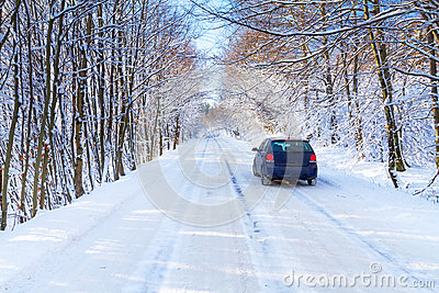 Snowy road in winter forest with single car