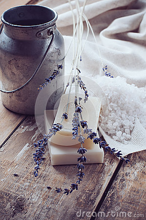 Soap, lavender, salt and old can on wooden board
