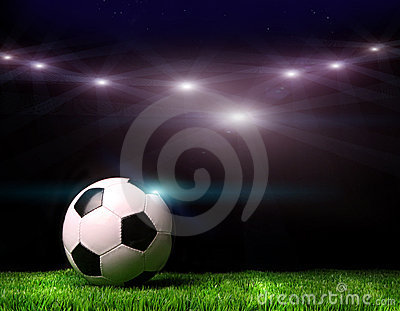 Soccer ball on grass against black