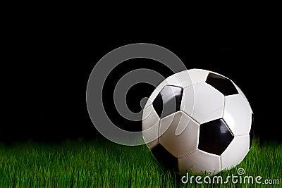 Soccer ball on grass over black