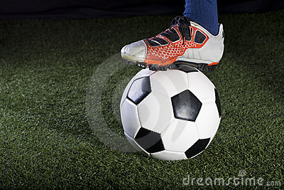 Soccer ball resting on a grass field at night