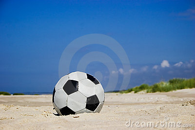 Soccer ball on sandy beach