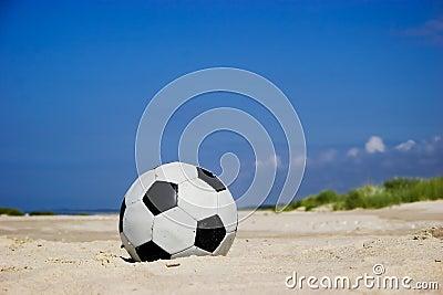 Soccer ball on sandy beach
