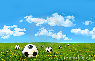 Soccer balls  in a field of  grass
