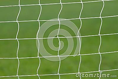 Soccer behind goal net