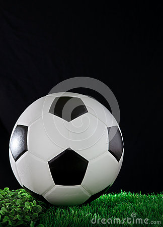 Soccer football on gree grass field with black bac