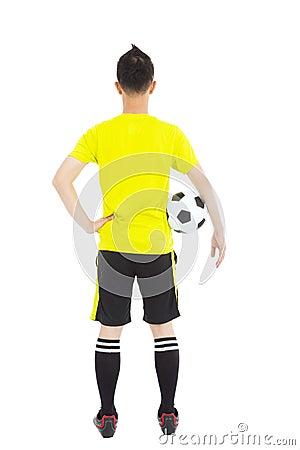 Soccer player holding a soccer next to  waist
