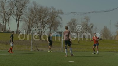 Soccer players practicing football on the pitch stock video