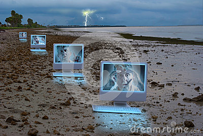 Four computers on a dark stormy beach
