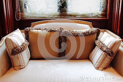 Sofa with pillows by the window