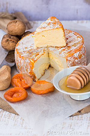 Free Soft Cheese With Cut Off Slice Creamy Texture, Orange Rind With Mold, French, German, Alps, Honey Dipper, Walnuts, Dried Apricots, Royalty Free Stock Photography - 86574697