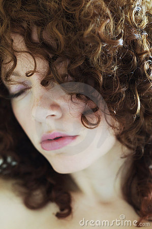 Soft focus face of curly haired brunette