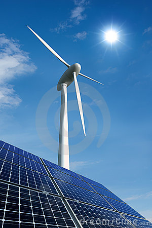 Solar panels and wind turbine against a sunny sky