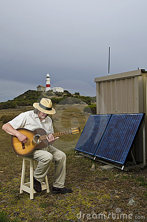 Solar Powered Guitarist With Lighthouse Royalty Free Stock Image - Image: 19772696