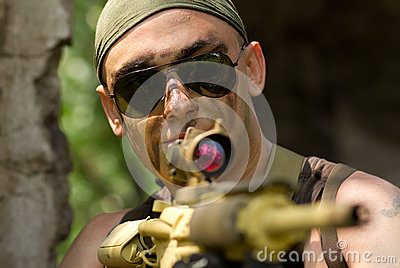Soldier in bandana targeting with a gun