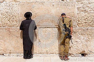 Soldier and orthodox jewish man pray at the western wall, Jerusalem Editorial Stock Image