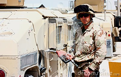 A soldier refueling a militay vehicle