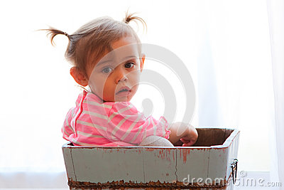 Solemn baby girl in wooden box