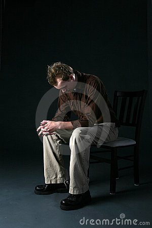 Solitary man sitting on chair with head down