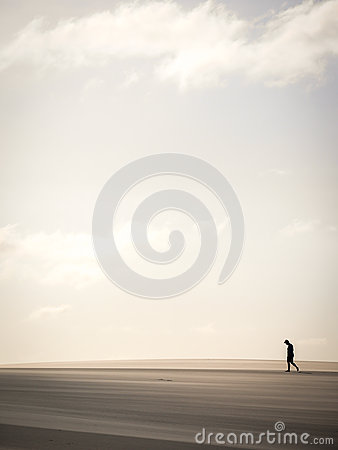 Free Solitary Man Walking Through Sand Dunes Stock Photography - 79795542