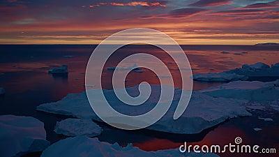 Solnedfryst kallt landskap med antarktiskt isberg i vatten på en lila kväll stock video